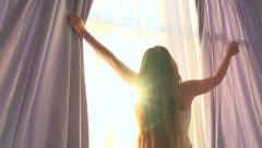 Beauty girl opens curtains on big window - stock footage