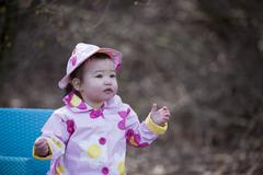 Little Girl in the Park Wearing Raincoat and Hat, Bethesda, Maryland, USA - stock photo