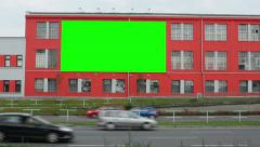 Billboard on the building in the city near road - green screen - passing cars Stock Footage