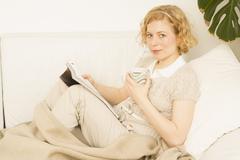 Portrait of Woman Sitting on Sofa Reading - stock photo