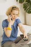 Woman using TV Remote - stock photo