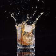 Ice Splashing into a Tumbler of Whiskey Stock Photos
