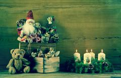 Vintage christmas decoration with santa and advent wreath on wooden backgroun Stock Photos