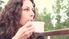 Young woman drinking coffee on the terrace of a cafe Stock Footage