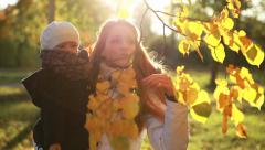 Young mother and daughter admire the yellow leaves in autumn park. - stock footage
