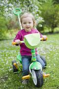 Little Girl Riding Three Wheel Bike - stock photo