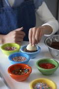 Stock Photo of Woman Dipping Shortbread into Chocolate and Sprinkles