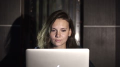 Girl working on computer in the evening in the interior with water background Stock Footage