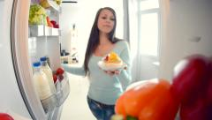 Beauty girl opens refrigerator door and puts delicious cake on shelf Stock Footage