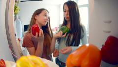 Cute pretty teenage girls in the kitchen next to fridge Stock Footage