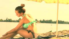 Beautiful smiling happy young woman with suntan cream - stock footage