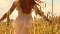 Beauty girl running on yellow wheat field. Happy woman outdoors. Harvest Stock Footage