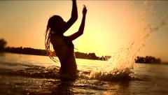 Teen girl swimming and splashing on summer beach over sunset Stock Footage