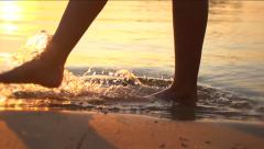 Woman walking on beach barefoot over sunset Stock Footage