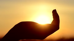 Hand catching a sun against beautiful sunset Stock Footage