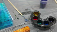 Accessories for Ebru drawing: oil paints, stick, wide paintbrush, close-up Stock Footage