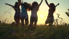 Group of happy teenage friends having fun outdoors, running and jumping Stock Footage