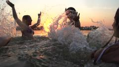 Group of happy teen girls playing in water at the beach Stock Footage