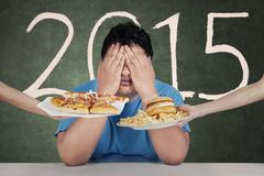 Stock Photo of overweight man avoid junkfood in 2015