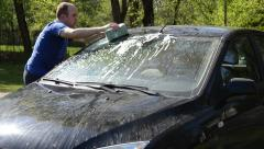 Young man carefully wash his favourite car windscreen and roof Stock Footage