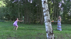 Pregnant woman with daughter girl play badminton game in park Stock Footage