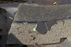 Stock Photo of Damaged Roof Shingles And Tar Paper Trash Pile