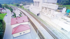 Train far away arriving at station aerial footage Stock Footage