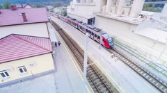 Electric train leaving station aerial flight over with panning Stock Footage
