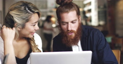 Young couple shopping online using digital tablet computer in cafe Stock Footage