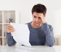 Horrified man reading a document Stock Photos