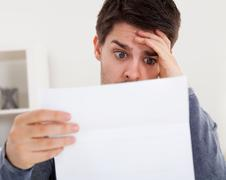 horrified man reading a document - stock photo