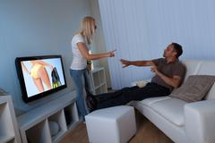 Wife preventing man watching female tv Stock Photos