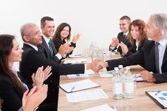 business team sitting at table and applauding - stock photo