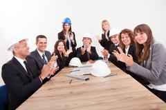 engineers sitting at table and applauding - stock photo