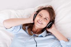 woman relaxing listening to music in bed - stock photo