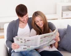 Both read article from newspaper Stock Photos