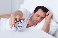 Exhausted man being awakened by an alarm clock Stock Photos