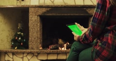 Back view of woman using electronic tablet by the fireplace. Shot in quality 4K Stock Footage