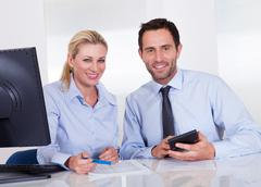 smiling accountants discussing reports - stock photo