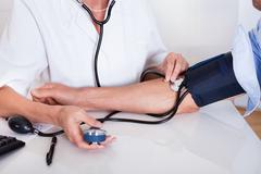 Doctor taking a patients blood pressure Stock Photos