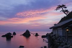 Pink sunrise and the Meoto Iwa wedded rocks at Ise Bay in Japan Stock Photos