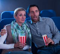 couple watching a movie reacting in horror - stock photo