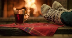 Woman relaxes by warm fire in woollen socks and having a cup of hot tea Stock Footage