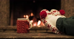 Woman relaxes by warm fire and wriggles her toes. Cozy evening by the fireplace Stock Footage