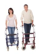 Mature couple using walking aide Stock Photos