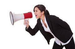 woman shouts through a megaphone - stock photo