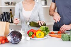 adding olive oil while cooking salad - stock photo