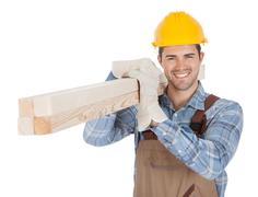worker wearing hard hat and carrying timber - stock photo