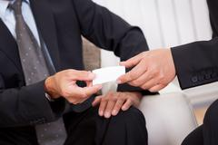 business card being passed over - stock photo