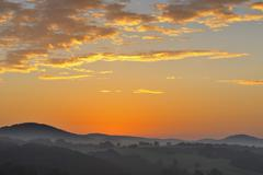 Orange sky at sunrise over hilltops and fields in Bavaria, Germany Stock Photos